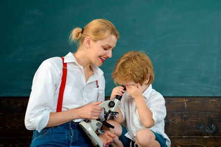 Science for children. The boy and his teacher. School and microscope. Look closer at things.