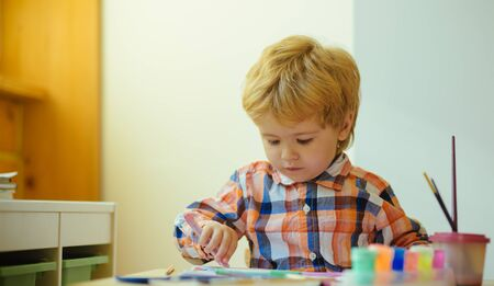 Little boy on drawing lesson. Serious kid enjoy painting with brush and colours wearing colourful shirt. Young child practice motor skils by drawing with pen. Developing activities for children.