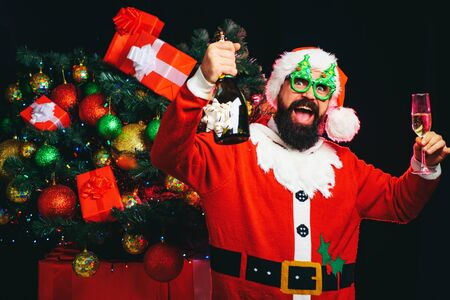 Happy Santa Claus in funny eyeglasses looking at camera. Alcohol and sparkling wine for holidays. Fun party. Corporate with cheerful Santa. Happy smile. Joy. Handsome funny man with bottle of wine. Stock Photo