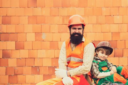 Happy team of builders. Father and son near a brick wall. Little builder helps his father. Family business. Reklamní fotografie