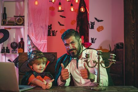 Happy family for Halloween. Father and son show thumbs up. Online Shopping for Halloween Parties.