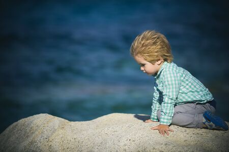 Traveling with the wind. Boy on the sea stones. Happy holidays on the coast.