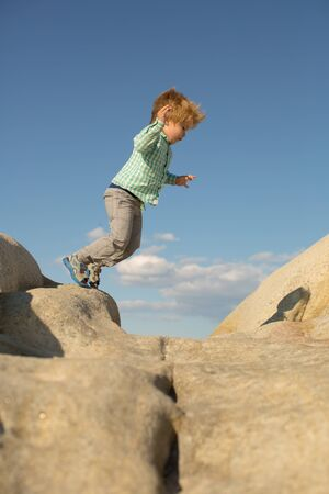 Summer activities. Leisure. The boy jumps on large stones near the sea. Nature and child. Zdjęcie Seryjne