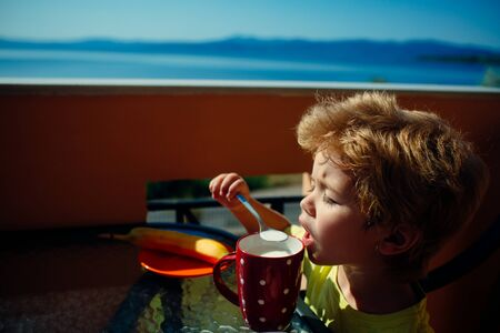 Appetite. The child eats milk porridge. Milk for breakfast. Healthy food for children. Summer breakfast on the terrace near the sea.