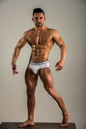 Strong handsome man pose on white background alone. Advertising concept of underwear for man. Healthy lifestyle and everyday exercises. Gym trainer. Naked bodybuilder with tanned skin. Man of dreams. 版權商用圖片