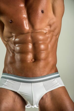Closeup body underwear for young man. Unrecognizable strong bodybuilder with six pack. Bodybuilder man with perfect abs, chest. Fashionable mens underwear, male penis in shorts. Sexy body sport guy.
