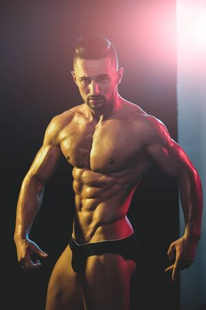 Strong athletic man shows body and abdominal muscles over dark background. Young handsome bodybuilder before sport competitions. Naked man with sexy hot body. Attractive guy poses with perfect body.