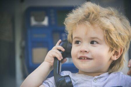 Communication, call on retro phone. Black handset in child little tender hand. Joyful boy speaks on the phone and looks somewhere far away. Amazement boy has landline conversation. Hi hello concept. Banco de Imagens