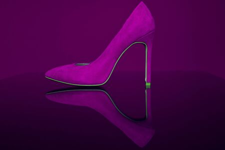 Shoe on a transparent surface. Advertising seductive shoes for sexy girls. Shop shoes. Evening shoes for theater, restaurant and cinema. Stylish girl and choice of shoes. Violet purple color close-up.