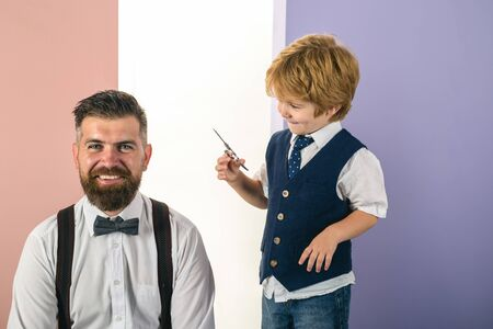 Happy son cuts fathers hair. Shaving man and razor man. Barber Shaves and Trims. Beard styling cut. Master hairdresser and style with scissors and comb. Male client getting haircut by hairdresser.