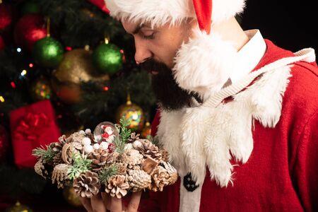 Weihnachtsmann mit Weihnachtsschmuck. Attraktiver Mann, der einen Weihnachtskranz in seinen Händen hält. Feiertage.