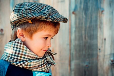 Shy child. The boy is looking down. Boy in a checkered cap. Little irish.