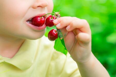 The child eats a cherry. Summer berries. Vitamins for children. Healthy food. 版權商用圖片
