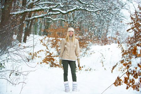 Winter style. Girl model in a snowy forest. Woman on a winter walk. Banco de Imagens