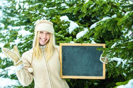Winter advertisement. Seasonal discounts. Girl holds a school board in the hands of a winter forest. Reklamní fotografie - 138202169