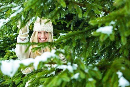 Hide and seek in the winter forest. The beautiful blonde. Woman in the forest with snow. Reklamní fotografie - 138202425