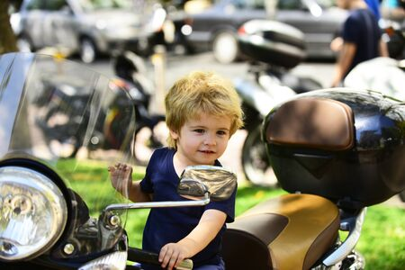 Small kid sits on motorbike and smiles. Sincere emotions from little boy. Motorbikes on street background. Street full of vehicles and happy child. Reklamní fotografie