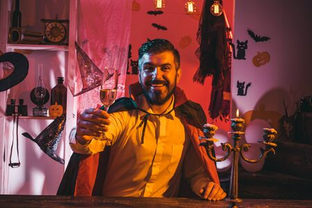 Happy Halloween. A glass of wine in the hand of an attractive man. Halloween party. Vampire is a ghost. A terrible holiday in October. Фото со стока