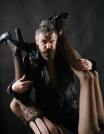 Man and womens legs. Sensual concept, seductive embrace. Bearded young guy hugs girls and legs upside down. Sexy relationships, toys and girlfriends. Polygamist. Polygamy, treason, wife and mistress