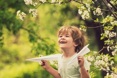 Spring game. Boy in the garden. Toy plane mood. Dream for children. Blossom trees walk.