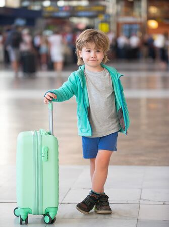 Happy traveler. The boy at the airport. A child with a turquoise suitcase. Ready to travel after quarantine.