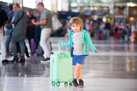 Road during quarantine and pandemic. Travels. Flight canceled. A boy with a suitcase in areport. Traveling with children. Return, way home. Child with hand luggage.