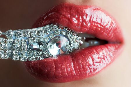 Close-up of beautiful womans lips with bright fashion dark red glossy makeup. Macro lipgloss cherry make-up. Mouth with wedding silver diamond ring. Jewelry accessories Фото со стока