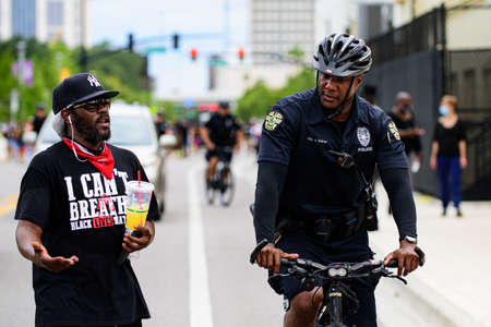 Orlando, FL, USA - JUNE 19, 2020: Black policeman on a bicycle and protester against racism in a T-shirt with an text I can not breathe.
