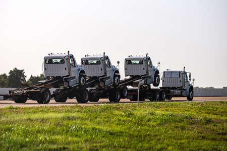 New trucks. Delivery of trucks. Highway caravan. Transport business.