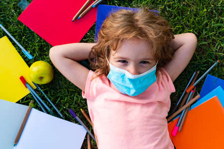 School supplies and apple for lunch. Distance learning in schools and kindergartens. Schoolboy in a mask against coronavirus. Stock fotó