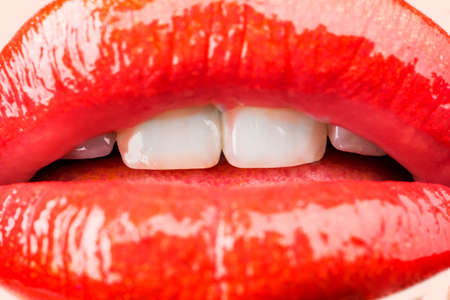 Passion. Sensual female lips. White healthy teeth. Mouth with teeth smile. Red lipstick and kiss. Lips close up.