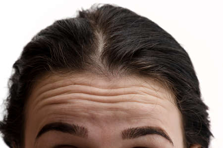 Woman looks in the mirror noticing the first wrinkles. Girl with wrinkles on forehead. Portrait of young woman with wrinkles on his forehead on white background. Do I have wrinkles?