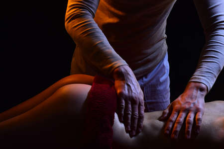Lumbar massage. The husband massages his wife. Strong hands and back pain