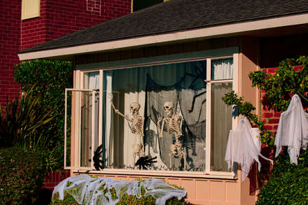 Skeletons in the window. Halloween scenery. Terrible holiday at home. Halloween in the USA. Traditions and house decor. Terrible creatures.