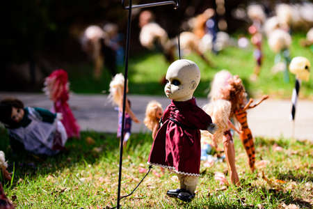 A scary doll is hung on a pole. Halloween scenery. Terrible holiday at home. Halloween in the USA. Traditions and house decor. Terrible creatures.