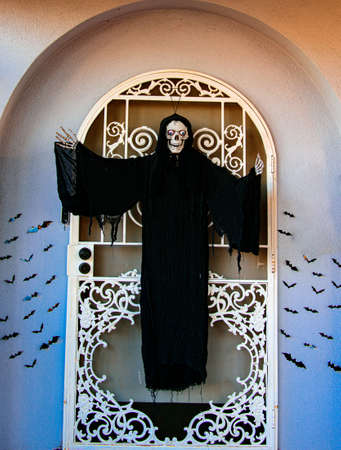 Death at the entrance to the house. Halloween scenery. Terrible holiday at home. Halloween in the USA. Traditions and house decor. Terrible creatures.