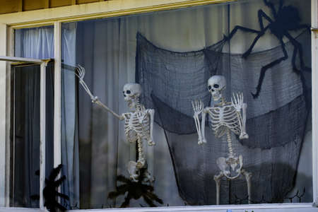 Skeletons waving from the window. Happy skeletons. Halloween scenery. Terrible holiday at home. Halloween in the USA. Traditions and house decor. Terrible creatures. 免版税图像