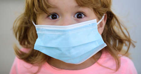 Scared child in a mask. Quarantine and coronavirus. Close-up portrait in a surgical mask. Pandemic. 免版税图像