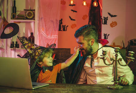 Funny family. Father and son are happy with online shopping. Happy family near laptop. Autumn holidays and Halloween. 免版税图像