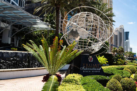 Sunny Isles, Florida, USA - May, 2020: Trump International Beach Resort. Globe sign and palm tree. Trumps business.