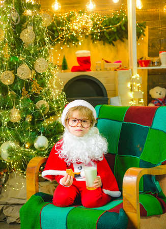 Santa Claus enjoying in served gingerbread man cake and milk. Christmas cookies and milk for child. Greeting card for kids Christmas. Santa child eating cookies and drinking milk. 免版税图像
