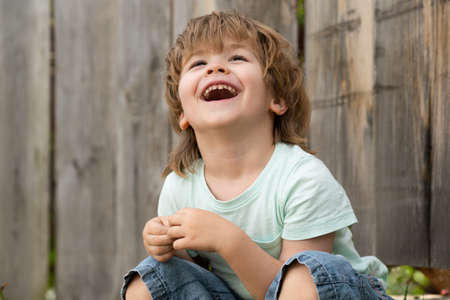 Real happiness. Happy smile. The boy is sitting in the garden and smiling. Childrens emotions. Beautiful child face.