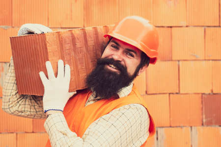 Happy builder with a brick. Construction site. New house. Dad is building a house. Man, husband. Mortgage. House for a family. House loan.