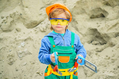Builder. The boy in the costume of the builder. Tools for building and repair. Safety glasses and hard hat. Safety at work. Child Builder repairman. Future engineer.
