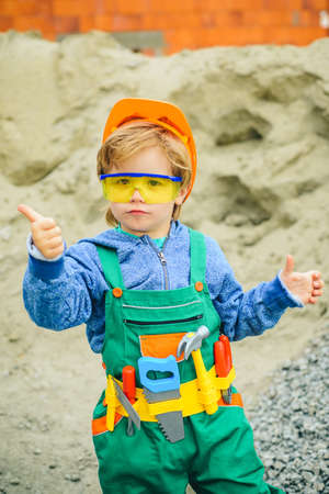 Little boy plays as builder. Concept of real estate and engineering. Successful worker boy with helmet giving thumb up isolated on gray background. 免版税图像