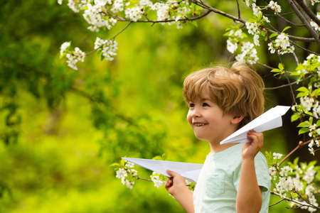 Happy boy in the garden with airplanes. Childhood in nature. 免版税图像