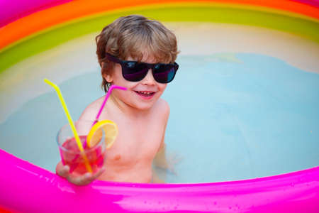 Cool happy holidays. Kid in the home pool. Cocktail.