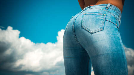Female buttocks in jeans on a sky background. 免版税图像