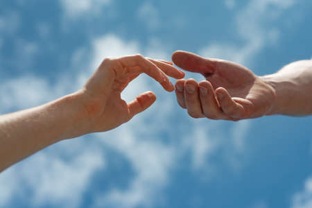Hands on sky background. Couple, love, together. 免版税图像