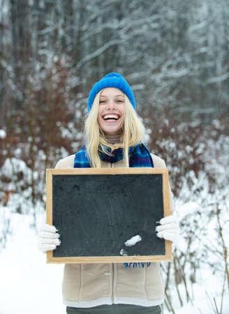 Winter advertising, sales, seasonal discounts. Girl with a billboard.